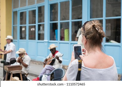 Havana, Cuba - 26 April 2018: Woman takes a photo with her smart phone of three local Cuban musicians play on the street busking for money. Two men play guitars and other man plays the timbales.
