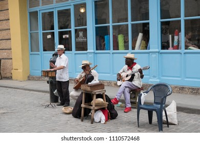 Havana, Cuba - 26 April 2018: Three local Cuban musicians play on the street busking for money. Two men play guitars and other man plays the timbales.