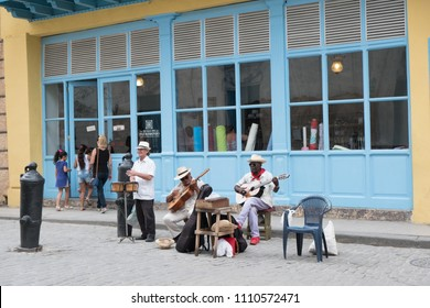Havana, Cuba - 26 April 2018: Three local Cuban musicians play on the street busking for money. Two men play guitars and other man plays the timbales in front of a fabric store in Old Havana.