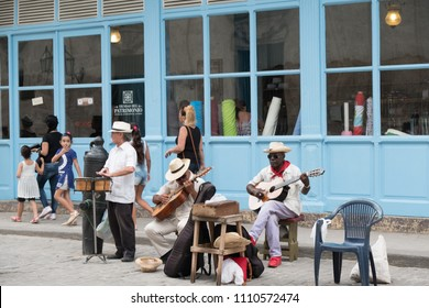 Havana, Cuba - 26 April 2018: Three local Cuban musicians play on the street busking for money. Two men play guitars and other man plays the timbales in front of a fabric store in Old Town Havana.