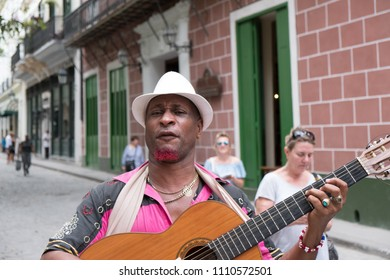 Havana, Cuba - 26 April 2018: Black Cuban man in a white fedora with a funny expression plays his classical guitar ad signs for American Tourists on the streets of Old Town Havana busking for money.