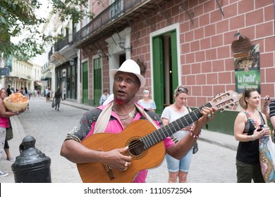 Havana, Cuba - 26 April 2018: Black Cuban man in a white fedora and funny expression plays his classical guitar ad signs for American Tourists on the streets of Old Town Havana busking for money.