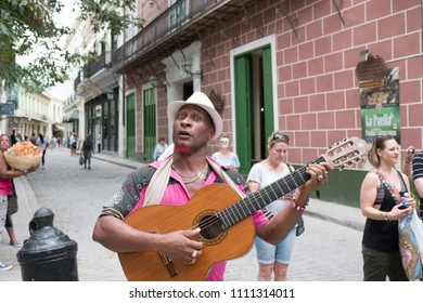 Havana, Cuba - 26 April 2018: Black Cuban man in a white fedora and goatee plays his classical guitar ad signs for American Tourists on the streets of Old Town Havana busking for money.