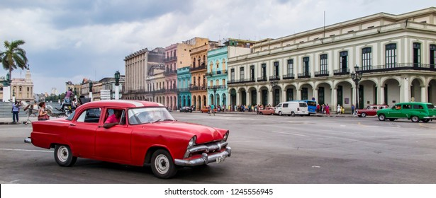 Havana / Cuba - 28 April 2015: An iconic panoramic street scene that captures the essence of Cuba: a red vintage American car stands out against a backdrop of brightly coloured historic buildings.