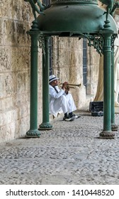 Havana / Cuba - 30 April 2015: Smartly dressed busker in a white suit, white trilby hat, black shoes with white spats sits on cobbled steps beneath a green metal awning and plays the trumpet.