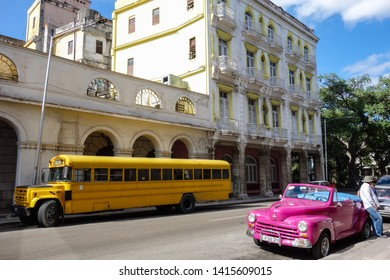 Havana, Cuba - 30th January 2018: Classic, old yellow schoolbus and a pink cabriolet parking in the streets of Havana