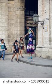 Havana, Cuba - 3.23.2017: A male stilt walker asking passersby for donation.