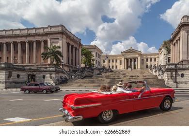 HAVANA, CUBA - APR 17, 2017: People in the American classic car in front of university Havana in Havana, Cuba
