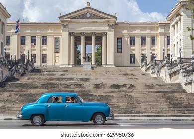 HAVANA, CUBA - APR 17, 2017: A blue American classic car driving in front of  University Havana in Havana, Cuba.