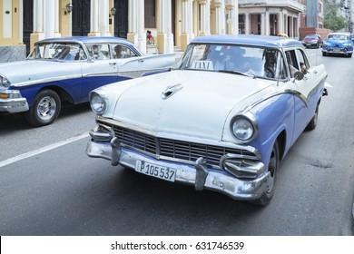 Havana, Cuba - April 03, 2017: American vintage cars driving in old Havana Cuba