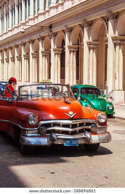 HAVANA, CUBA - APRIL 1, 2012: Taxi driver meets tourist on Orange Cadillac Series 62 cabriolet