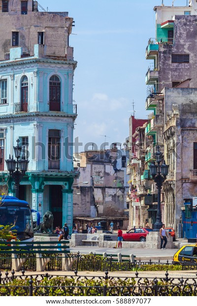 HAVANA, CUBA - APRIL 1, 2012: Cubans walk the streets of the old town with the destroyed beautiful houses