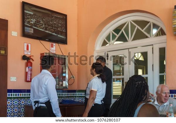 Havana / Cuba - April 18, 2018: Cubans watch Cuban TV on a rooftop bar in Havana as Raul Castro cedes power to Miguel Díaz-Canel.