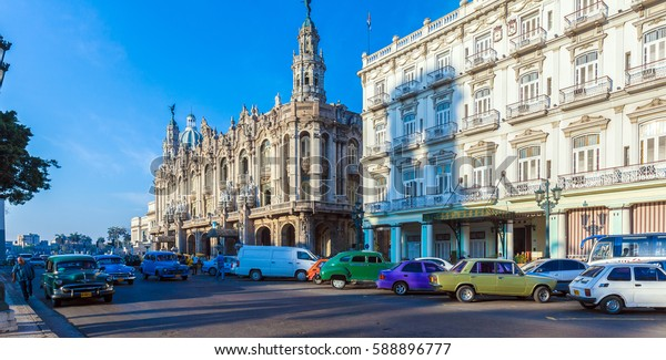 HAVANA, CUBA - APRIL 2, 2012: Two vintage cars on the road in front of Great Theater