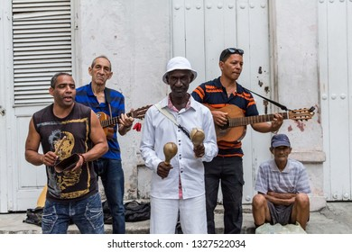 Havana, Cuba - April 4, 2016: Older Cuban musician playing some traditional instruments and guitars on the street. Latin music. Street music.