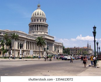 Havana, Cuba - August, 2004: Unidentified participants walking in fornt of El Capitolio, or the National Capitol Building of Cuba.