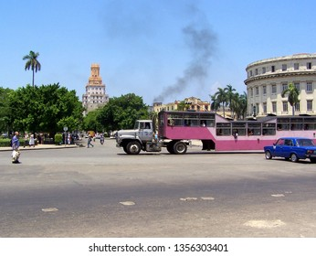 Havana, Cuba - August, 2004: Unidentified participant being passed by a public transport truck (El Camello metrobus) in the center of Havana, Cuba.