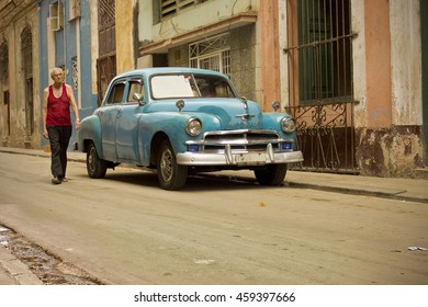 HAVANA, CUBA - CIRCA JULY 2016: Afternoon along a historic street in Havana, Cuba with man walking by classic old American car.