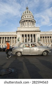 HAVANA, CUBA - CIRCA JUNE, 2011: Pedestrians pass in front of classic American car near the Capitolio building in Central Havana.