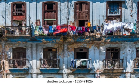 Havana Cuba: Clothes hanging in front of a window with ornate architectural detail. A typical old house in colonial style on central Havana, wet clothes are drying in the wind, hanging in the balcony.
