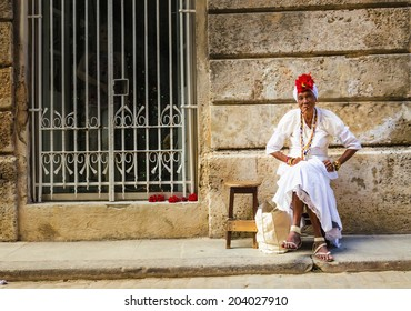 HAVANA, CUBA - DECEMBER 1, 2013:  Old black lady dressed in typical cuban clothes smoking a huge cuban cigar next to the Havana Cathedral.