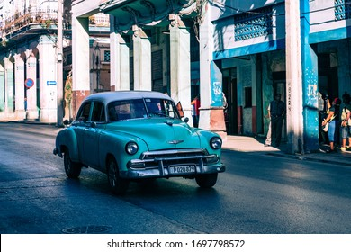 HAVANA, CUBA - DECEMBER 10, 2019: Havana Cuba Classic Cars. Typcal Havana urban scene with colorful buildings and old cars.