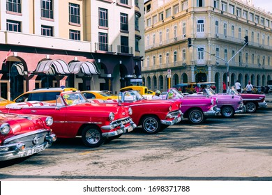 HAVANA, CUBA - DECEMBER 10, 2019: Vintage classic american car in Havana, Cuba. Typical Havana urban scene with colorful buildings and old cars.