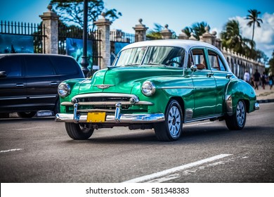 Havana, Cuba - December 15, 2012: HDR - Streetlife with a green american Chevrolet vintage car with white roof on the Malecon in Havana- Serie Cuba Reportage