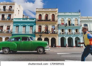 Havana, Cuba - December 15, 2019: A green vintage car and a gentleman crossing a street in Havana, Cuba