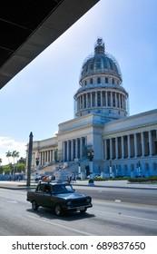 Havana, Cuba - December 19, 2016: Retro cars pass the Capitol building (El Capitolio) in the heart of Habana Vieja (Old Havana) in Cuba