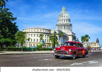 HAVANA, CUBA - DECEMBER 2, 2013: Old classic American maroon car rides in front of the Capitol. Before a new law issued on October 2011, cubans could only trade cars that were on the road before 1959.