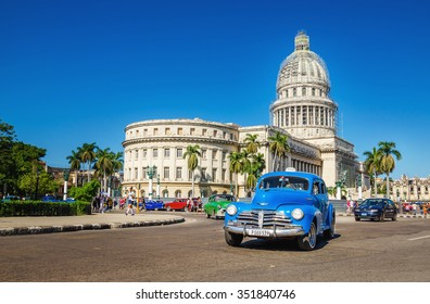 HAVANA, CUBA - DECEMBER 2, 2013: A typical Cuban image, an old classic American blue car on the background of National Capitol Building in Havana, Republic of Cuba, Central America