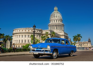 HAVANA, CUBA - DECEMBER 2, 2013: An old classic American blue car on the background of National Capitol Building in Havana, Republic of Cuba, Central America