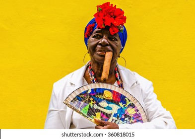 HAVANA, CUBA - DECEMBER 2, 2013: The typical image of Cuba, an old Cuban dressed in traditional dress posing with a big cigar in her mouth, Havana, Cuba, Central America