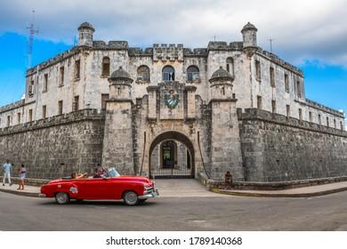 HAVANA, CUBA - DECEMBER 26, 2017: Tourists enjoy a ride around Castillo de la Real Fuerza in an iconic automobile.