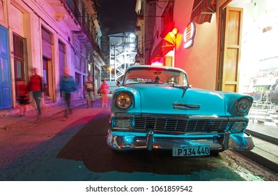 Havana, Cuba - December 29, 2017: A 1956 Chevrolet is parked in front of a restaurant on a small street in Havana. A vibrant night life and 1950s era cars are popular attractions in the island nation.