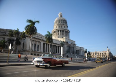 havana, cuba - december 7th, 2017: view of the capitolio with a vintage red car in la havana