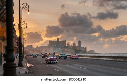 Havana, Cuba - February 1, 2018: Classic American cars on the Malecon in Havana at sunset. Recent law allows Cubans to trade cars, the former law led to a fleet of private owned cars from the 50's.