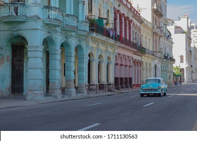 Havana, Cuba - Jan 10, 2020: street scene - old 1950s American car passing by crumbling colorful colonial buildings facades with columns and terraces. Selective focus. Sightseeing, tourism concept.