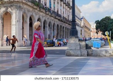 Havana, Cuba - Jan 10, 2020: African Cuban woman in a red dress walking on a street, Old colonial buildings with columns and terraces in the background. Selective focus, sunny day.