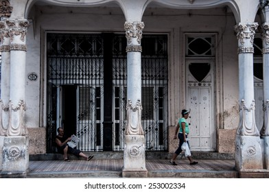 HAVANA, CUBA - JANUARY 1, 2014:  A Cuban woman is walking on the street of Old Havana, Havana, Cuba. Old Havana is city-center and one of the 15 municipalities forming Havana, Cuba
