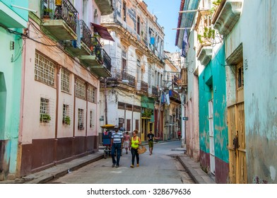 HAVANA, CUBA - JANUARY 1, 2014: Tourists are walking on the street of Old Havana in Havana, Cuba. Old Havana is the city-center and one of the 15 municipalities forming Havana, Cuba.