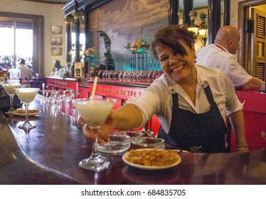 HAVANA, CUBA - JANUARY 14, 2016: Image with blur motion and blurred background of a waitress serving daiquiris in the bar Floridita, in the tourist center of the city