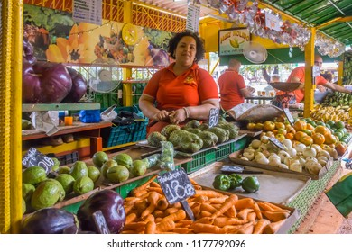Havana, Cuba - january 15, 2016: Young woman tending inside a fruit and vegetable stand in the agricultural market of a populous neighborhood of the city