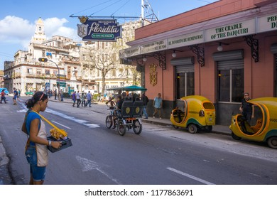 Havana, Cuba - january 15, 2016: Scene with a young itinerant potato seller, with tricycles and coconut taxis in front of the Floridita bar in the historic center of the city