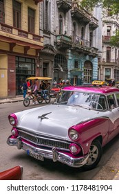 Havana, Cuba - january 15, 2016: Scene in a street of the historical center of the city with old American vehicles parked and cycle taxis circulating among neglected buildings