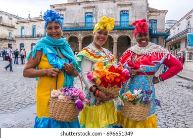 HAVANA, CUBA - JANUARY 19, 2016: Three women dressed in traditional costumes of the island, walk with baskets of flowers across the cathedral square, in the historic center of the city