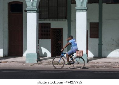 HAVANA, CUBA - JANUARY 20, 2016: A man riding a bicycle through the streets of the city