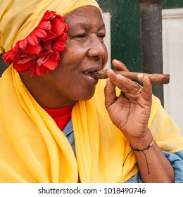 Havana, Cuba - January 21, 2018: Portrait of a woman with cigar in Havana, Cuba. With two million visitors per year these iconic characters are an attraction in  Cuba.
