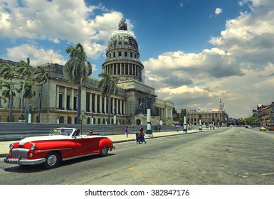 HAVANA, CUBA - July 10, 2015: Old classic american red car on the background of the National Capitol Building in Havana, Cuba. Vintage style photo